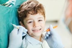 Child smiling while sitting in the dentist`s chair. Beautiful child smiling while sitting in the dentist`s chair. Close-up royalty free stock images