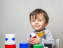 Child smiling to the camera. Child staring at the camera smiling while playing with toys Royalty Free Stock Photo