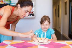 Child smiling watching woman lighting candles on birthday cake Stock Images