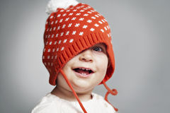 Child smiling in winter red hat. On the background Stock Images