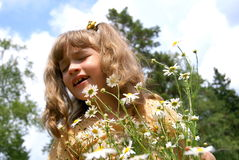 The child sneezes. The girl stands in the summer in park about flowers and sneezes Stock Images
