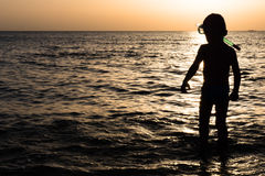 Child with snorkel and mask for diving on background of sea sunset Stock Photo