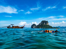 Child snorkeling in Andaman Sea with longboat and karst cliff in Royalty Free Stock Photos