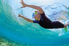 Child in snorkeling mask dive underwater in blue sea lagoon stock photo