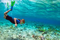 Child in snorkeling mask dive underwater in blue sea lagoon stock photos