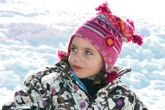 Child in the snow. A young caucasian child sitting in the snow wrapped up warmly Royalty Free Stock Images