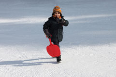 Child in the snow. With red sleigh shovel Stock Image