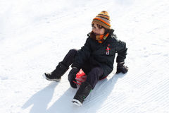 Child in the snow. Child is flatten with a sled down the hill on the ski trail in winter resort Stock Photography