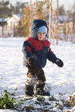 Child in snow. A little child wearing winter clothes walking in the snow Stock Image