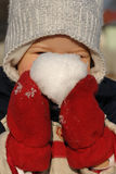 Child with snow ball. Child holding a snow ball with red gloves Stock Photo