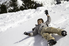Child on snow hill that rolls Stock Image