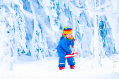 Child with snow shovel in winter. Cute little child, funny toddler girl in a colorful snowsuit and hat playing with a snow shovel in a beautiful winter park Royalty Free Stock Photography