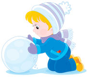 Child with a snowball. Little boy or girl made a big snowball to make a snowman Royalty Free Stock Photo