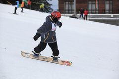 A child snowboarding on a mountain slope. Arena Platos, Paltinis, near Sibiu, Romania - 2 February 2013: Arena Freestyle Open - Ski and Snowboard competition Royalty Free Stock Photos