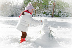 Child and snowman. Winter scene with child making a snowman Royalty Free Stock Photos