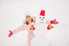 Child and snowman in winter Royalty Free Stock Photo