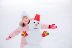 Child and snowman in winter Stock Photography