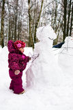 Child with snowman in winter park Royalty Free Stock Photography