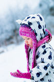 Child in snowy day. Baby girl in white snowsuit and pink hat looking on the gloves with snow. Stock Image