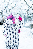 Child in snowy day. Baby girl in white snowsuite and pink hat, boots  gloves in the snow winter park. Stock Photos