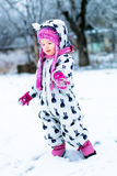 Child in snowy day. Baby girl in white snowsuite and pink hat, boots  gloves in the snow winter park. Royalty Free Stock Photo