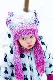 Child in snowy day. Baby girl in white snowsuite and pink hat, boots  gloves in the snow winter park. Stock Photo
