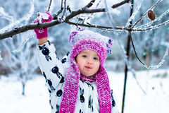 Child in snowy day. Baby girl in white snowsuite and pink hat, boots  gloves in the snow winter park. Happy. Royalty Free Stock Photo