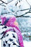 Child in snowy day. Baby girl in white snowsuite and pink hat, boots  gloves in the snow winter park. Happy. Royalty Free Stock Image