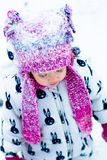 Child in snowy day. Portrait of baby girl in white snow suit and pink hat in the winter park.  in . Royalty Free Stock Photography