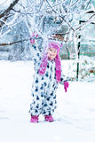 Child in snowy day. Snow falls from the tree. Baby girl in white snowsuite and pink hat, boots  gloves in the winter park.  Happy. Royalty Free Stock Image