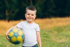 Child with a soccer ball under his arm at house garden with grass background, smiling. Kid Sport and Soccer World Cup. Child with a soccer ball under his arm at Stock Photos