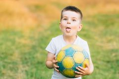 Child with a soccer ball under his arm at house garden with grass background, smiling. Kid Sport and Soccer World Cup. Child with a soccer ball under his arm at Royalty Free Stock Photography