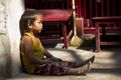 Child solitude. Poverty through Childs eye. This images has been taken in a little village in Myanmar (Burma), near a monastery Stock Image