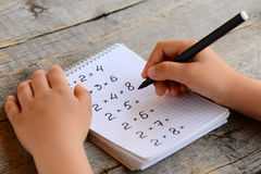 Child solves math examples. Child holds a marker in his hand and writes answers to multiplication examples in a notebook Royalty Free Stock Image