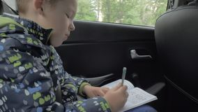 Child solving chess puzzles during car travel stock video footage