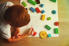 Child solving labyrinth, building from plastic blocks Royalty Free Stock Photography