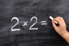 Child solving math problem on the blackboard. Multiplication royalty free stock image
