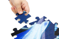 Child solving puzzle. Child hand with a piece of puzzle putting together Royalty Free Stock Photo