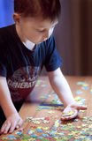 Child Solving a Puzzle - Education. Child Solving a Puzzle on a Table Stock Image