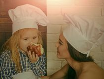 Child son eating bread bun with mother. Woman and boy in chef hats in kitchen. Healthy food and diet. Homemade baking and cooking. Happy family and mothers day royalty free stock image