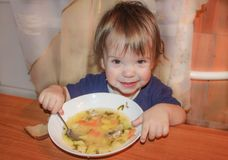 The child is a soup from a plate. A little boy eats his own soup stock photos