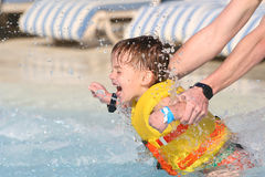 The child and sparks of water. The child in a life jacket and sparks of water Stock Photo