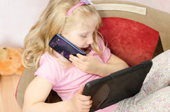 Child speaking by mobile and playing in tablet Stock Photos