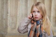 The child speaking on the phone. Looking surprised Stock Image
