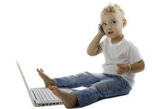 Child speaking on the phone. Child sitting on the floor with phone and laptop Royalty Free Stock Photos