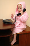 The child speaks on the phone. The child in a dressing gown speaks on the phone royalty free stock image