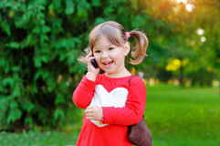 Child speaks on the phone in the park.  royalty free stock photography