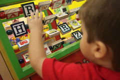 Child with spelling toy. A child flips letters as he learns to spell stock photos