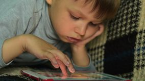 Child spending leisure time with tablet PC stock footage
