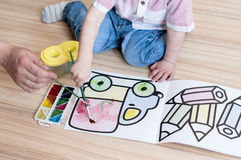 A child spends time with an adult drawing with watercolors. On floor stock photo